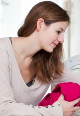 Junge Frau kniet vor der Waschmaschine