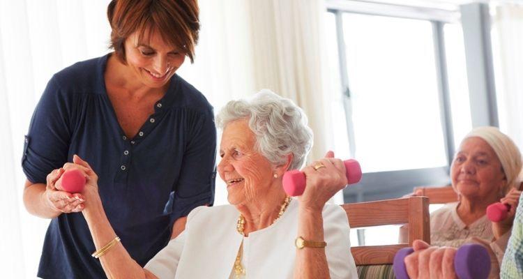Pflegerin untersützt ältere Dame beim Heben von leichten Gewichten
