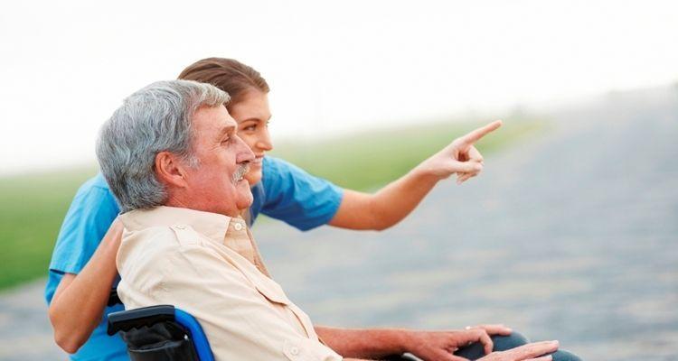 Pflegerin zeigt ihrem Patienten im Rollstuhl etwas