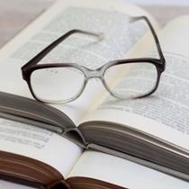 Brille auf einem offenem Buch